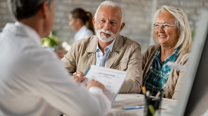 Happy senior couple going through medical insurance paperwork with a doctor.